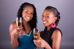 La tenencia de la mujer africana hermosa joven al vidrio de champán Foto de archivo libre de regalías