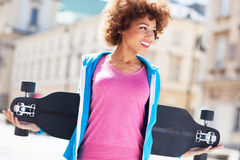 La tenencia de la mujer joven patina sobre ruedas Foto de archivo libre de regalías