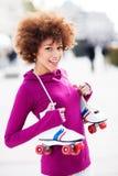 La tenencia de la mujer joven patina sobre ruedas Imagenes de archivo