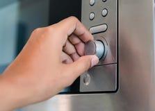 La tenencia de la mano gira el calor del botón del círculo del dial del horno de microondas para cocinar foto de archivo