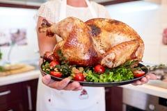 La tenencia de la mujer del primer adornada asó el pavo en un fondo de la cocina Concepto del pavo de la acción de gracias fotografía de archivo