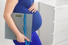 La tenencia de la mujer embarazada escala cinta métrica Fotos de archivo