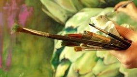 La tenencia del pintor del artista profesional cepilla en su mano que dibuja ilustraciones con las pinturas de aceite