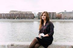 La tenencia elegante joven de la muchacha del inconformista se lleva la taza de café mientras que se sienta en el embarcadero del Fotografía de archivo