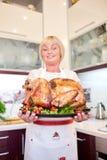 La tenencia feliz de la mujer adornada asó el pavo en un fondo de la cocina Concepto del pavo de la acción de gracias Copie el es Imagen de archivo libre de regalías