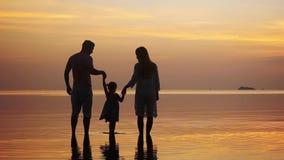 La tenencia joven feliz de la familia se da que camina a lo largo de la orilla durante sorprender puesta del sol de oro Día de fi almacen de video