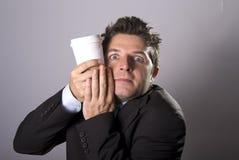 La tenencia maniaca del hombre de negocios del adicto se lleva el café en el apego del cafeína imagen de archivo