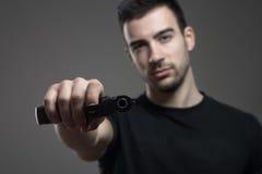 La tenencia peligrosa del criminal inclinó el arma que amenazaba teniendo como objetivo la cámara Fotos de archivo libres de regalías