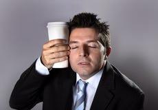 La tenencia soñolienta del hombre de negocios del adicto se lleva el café en el apego del cafeína imágenes de archivo libres de regalías
