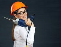 La tenencia sonriente del constructor de la mujer de negocios perfora la herramienta en hombro fotografía de archivo libre de regalías