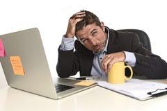 La tensión agotada del sufrimiento del hombre de negocios en el escritorio del ordenador de oficina abrumó cansado fotografía de archivo