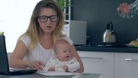 La tensión de la familia, niño interfiere con la madre cansada de trabajo con el niño en la cocina almacen de metraje de vídeo