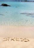 La tensión de palabra escrita en la arena, quitada por las ondas, relaja concepto Foto de archivo libre de regalías