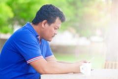 La tensión del hombre mientras que siéntese mirando el teléfono elegante Imagen de archivo
