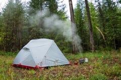 La tente dans le bois et l'eau bout dans le pot au brûleur à gaz Images libres de droits