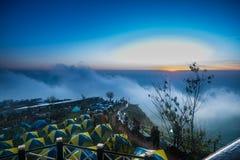 La tente de camping sur la montagne et le lever de soleil brumeux aménagent en parc pendant le matin Photo stock