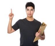 La tenuta asiatica dell'uomo con la cartella ed il dito indicano su Fotografie Stock Libere da Diritti