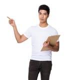 La tenuta asiatica dell'uomo con la lavagna per appunti ed il dito indicano su Fotografie Stock