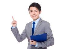 La tenuta asiatica dell'uomo d'affari con la lavagna per appunti ed il dito indicano su Fotografia Stock