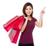 La tenuta asiatica della donna con il sacchetto della spesa ed il dito indicano su Immagine Stock Libera da Diritti