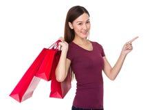 La tenuta asiatica della donna con il sacchetto della spesa ed il dito indicano su Fotografia Stock