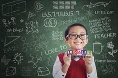 La tenuta asiatica dello studente del ragazzo impara il blocco nella classe Fotografie Stock Libere da Diritti