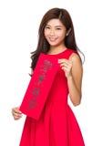 La tenuta cinese della donna con il chun di fai, significato di frase è eccelle il vostro Fotografie Stock