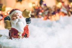 La tenuta del Babbo Natale la campana e la stella sta fra il mucchio di neve alla notte silenziosa, accende la speranza e la feli Immagini Stock