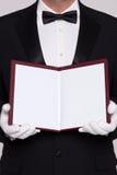 La tenuta del cameriere apre un menu in bianco fotografie stock