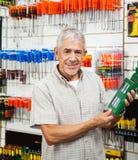 La tenuta del cliente ha imballato il prodotto nel negozio dell'hardware Fotografia Stock