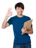 La tenuta del giovane con la lavagna per appunti ed il segno giusto gesture Fotografie Stock Libere da Diritti