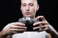 La tenuta del giovane nella sua passa la vecchia macchina fotografica della foto Immagine Stock