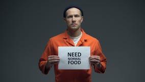 La tenuta del prigioniero maschio ha bisogno del segno normale dell'alimento, maltrattamento in prigione, affamata video d archivio