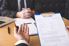 La tenuta del reclutatore o del datore di lavoro che legge un riassunto durante circa il suo profilo del candidato, datore di lav fotografia stock