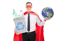 La tenuta del supereroe ricicla il recipiente e la terra Fotografia Stock