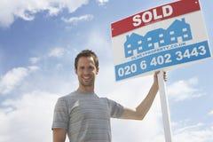 La tenuta dell'uomo ha venduto il segno contro il cielo Fotografia Stock