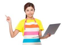 La tenuta della casalinga con il computer portatile ed il dito indicano su immagine stock