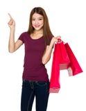 La tenuta della donna con il sacchetto della spesa ed il dito indicano su Immagini Stock