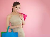 La tenuta della donna di acquisto insacca su fondo rosa, ragazza asiatica Fotografia Stock