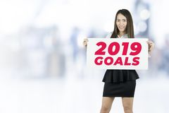 La tenuta della donna di affari affigge 2019 scopi firma immagini stock libere da diritti