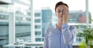 La tenuta della donna di affari consegna un occhio in ufficio che è stanco fotografie stock libere da diritti