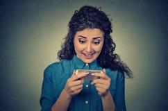 La tenuta della donna facendo uso di nuovo telefono cellulare dello smartphone ha collegato Internet di lettura rapida Fotografie Stock Libere da Diritti