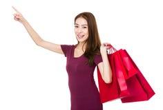 La tenuta della giovane donna con il sacchetto della spesa ed il dito indicano su Fotografia Stock Libera da Diritti