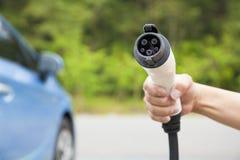 La tenuta della mano inserisce il connettore per il carico dell'automobile elettrica Fotografie Stock Libere da Diritti