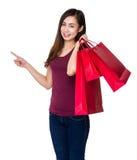 La tenuta della ragazza con il sacchetto della spesa ed il dito indicano su Fotografie Stock Libere da Diritti