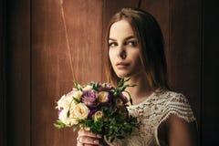 La tenuta della ragazza fiorisce in mani, giovane bella sposa nel mazzo bianco di nozze della tenuta del vestito, mazzo della spo Fotografie Stock