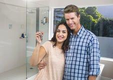 La tenuta delle coppie digita il bagno domestico immagini stock libere da diritti
