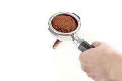 La tenuta di barista il portafilter con il fondo di caffè, prepara tamp Fotografie Stock Libere da Diritti