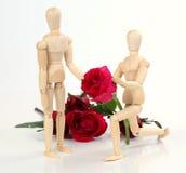 La tenuta di legno dell'uomo della figurina e dare sono aumentato all'amante con sono aumentato b Fotografia Stock Libera da Diritti