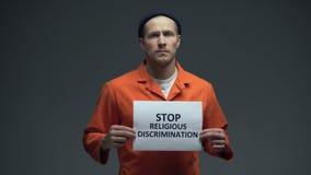 La tenuta europea del prigioniero maschio ferma il segno di discriminazione religiosa, pressione stock footage
